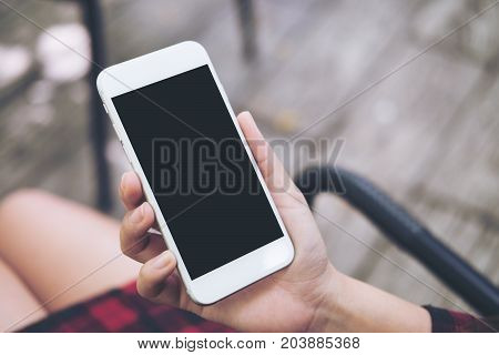 Mockup image of a woman's hand holding white mobile phone with blank black screen on thigh with wooden floor background in vintage cafe