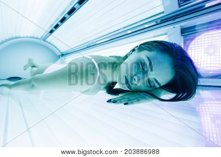 Beautiful sexy young woman tanning in solarium