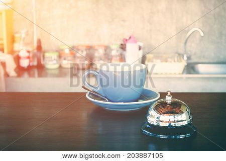 bell and hot coffee cup on coffee shop counter for alert or wark up concept