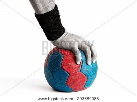 Man's hand pressing down on blue and red handball isolated on white colored handball desaturated hand