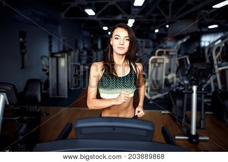 Young fitness woman doing cardio exercises at the gym running on a treadmill. Female runner training at the health club.