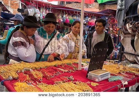 April 29 2017 Otavalo Ecuador: indigenous quechua women in front of a jewelry stand in the Saturday market