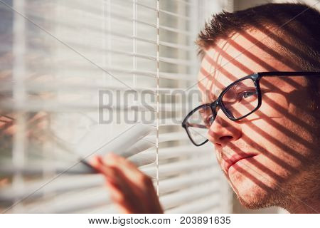 Curious man with eyeglasses looking through a jalousie. Themes curiousity surveillance or eyesight.