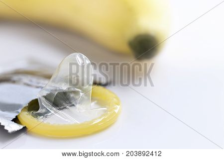condom with a yellow banana on white background. with copy space for text.