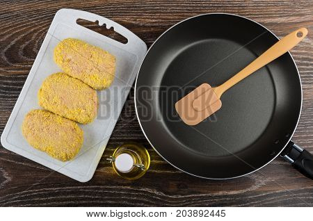 Raw Cutlet On Cutting Board, Frying Pan, Spatula And Oil