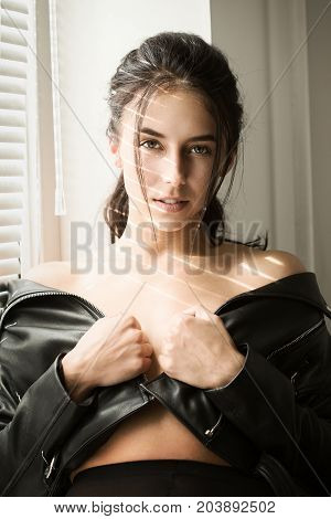 sensual girl show her shoulders near window with blinds