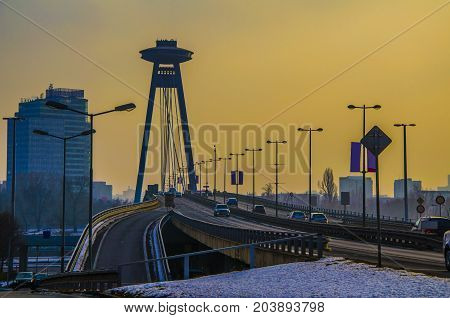 dusk on the new bridge of bratislava is observed at the top of the structure that holds the tensors of the bridge a construction a restaurant point of view of the city