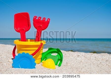 Yellow baby bucket with red handle, plastic red spatula and rake, green sieve, yellow sand form of strawberry, blue plate, blue sea and sky, yellow sand beach seashells seaside summer vacation sunny