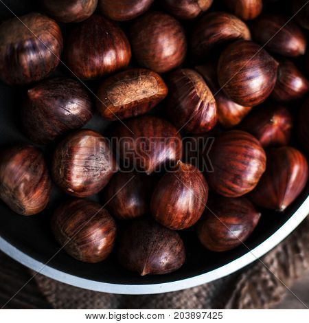 Brown chestnuts in a frying pan on old wooden table close up with copy space. Roasted Chestnuts for Christmas