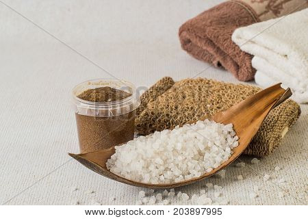 Skin care products. Sea salt a jar with a cosmetic body scrub loofah and terry towels on a light background.