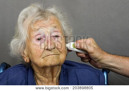 Senior Citizen having Temperature Checked. Senior lady having a temperature check with a digital ear thermometer by a health care worker.