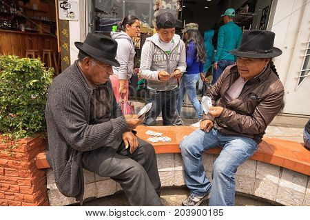 May 6 2017 Otavalo Ecuador: indigenous quechua men playing cards on the street in the Saturday market