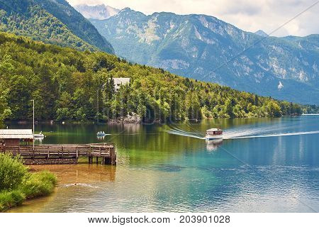 Small ship arrives to the wooden quay at lake Bohinj on a sunny day