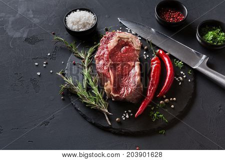 Raw rib eye steak with herbs and spices. Cooking ingredients for restaurant dish. Fresh meat with chilli and knife on plate on black background.