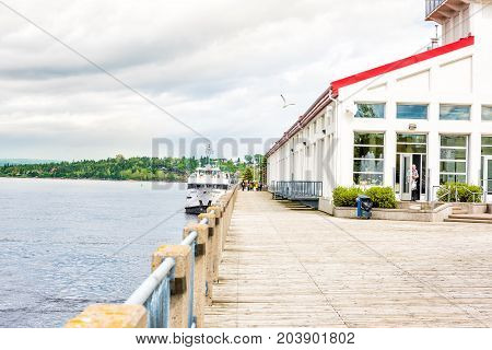 Saguenay Canada - June 3 2017: Sidewalk terrace boardwalk in downtown city park in Quebec during summer with river and tour boat and people walking