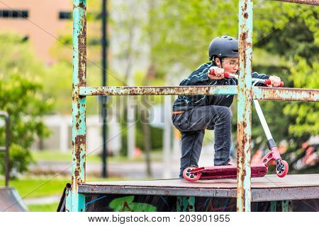 Saguenay Canada - June 3 2017: Downtown city summer park in Quebec with young teenager boy climbing on top of metal rusty playground ramp in skatepark on scooter