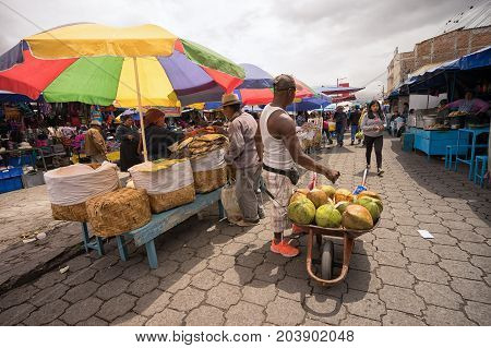 May 6 2017 Otavalo Ecuador: man selling coconut drink from wheelbarrow in the Saturday market