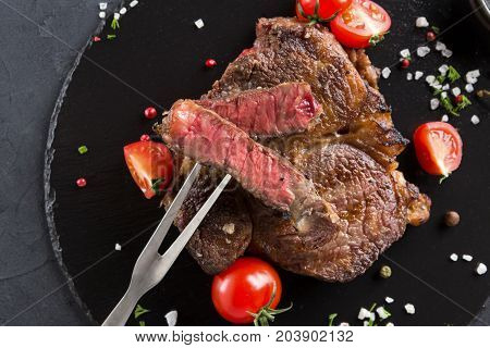 Rare rib eye steak with meat fork on dark plate, decorated with tomatoes and spices and meat fork, closeup