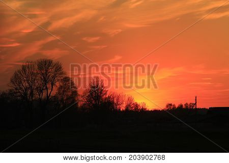 dark sunset with crimson clouds in the sun beams