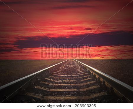 rails going away into the fiery red sunset. rails going away into the dark landscape with fiery red sunset