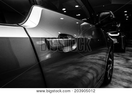 BERLIN - NOVEMBER 28 2014: Showroom. A fragment of the BMW i3 previously Mega City Vehicle (MCV) is a five-door urban electric car developed by the German manufacturer BMW. Black and white.