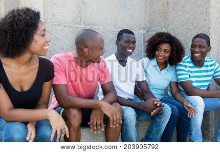 Laughing and talking group of african american men and women outdoors in the summer