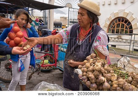 May 6 2017 Otavalo Ecuador: produce vendor in the Saturday market giving change to costumer