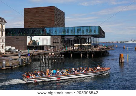 Copenhagen Denmark - August 24 2017: A sightseeing canal tour boat at Nyhavn in front of the Royal Danish Playhouse (Skuespilhuset).