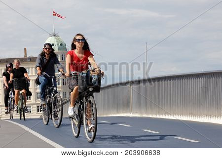 Copenhagen Denmark - August 24 2017: A group of three cyclists cycles over the bridge Inderhavnbroen.
