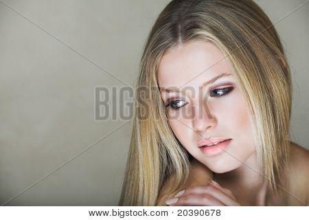 Young beautiful teenage girl with long blond hair and blue eyes in low key effect