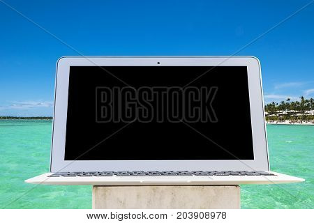 Laptop computer on wooden table. Top ocean view. Tropical island background. Open blank laptop computer empty space. Front view with copy space. Empty space for text
