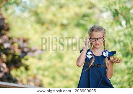 Adorable little school girl with notes and pencils outdoor.