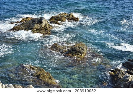 The cliff descends into the sea, many splashing waves and stones