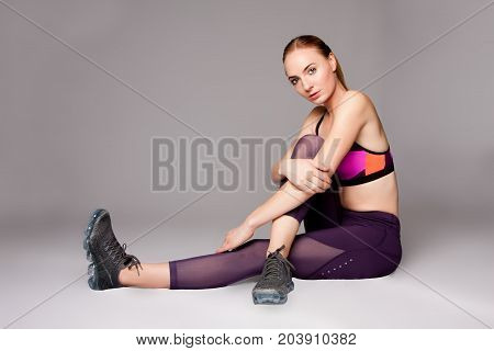 Beautiful athletic sports woman sitting on floor.