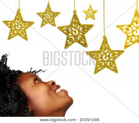 African woman looking at gold Christmas ornament stars with lace pattern isolated on white