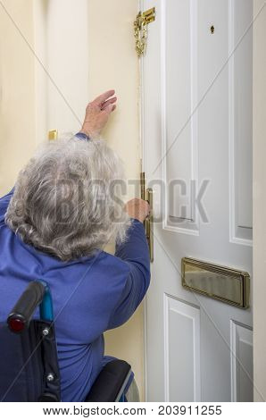 Disabled Senior Lady trying to open a door. Image of a senior disabled lady in a wheelchair trying to reach and take a safety chain off a door.