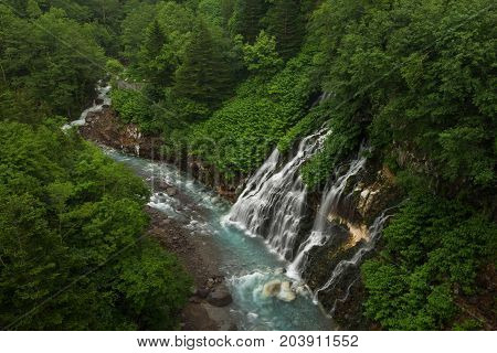 Beautiful Shirogane Falls dropping into a blue river, Biei, Hokkaido, Japan
