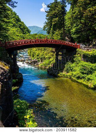 NIKKO, JAPAN - AUGUST 14, 2017 : Red Ancient Bridge, the Shinkyo bridge over the Daiwa river on a beautiful sunny day, World heritage site, Nikko Tochigi Japan.