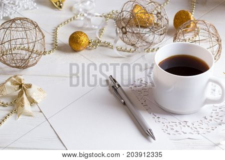 Holidays background. Blank paper Christmas card with cup of coffee on wooden table. copyspace of winter and Christmas concept