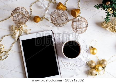 Holidays background. with cup of coffee on wooden table. Digital tablet and Christmas golden decorations on wooden background