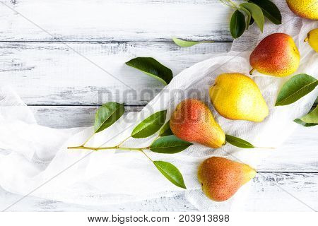 Summer romantic still life. Fresh ripe organic Pears with leaves. Soft style high key photo. White table surface for background. Natural vegetarian and diet food. Fruit concept. Summer season garden.