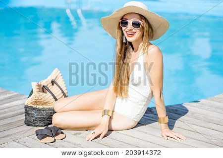 Beautiful young woman in sunhat relaxing near the swimming pool sitting with bag and slippers on the wooden poolside