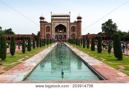 Agra, India - 12th Aug 2017: Crowds roam on the path leading to the entry gate for the Taj Mahal complex. The beautiful mughal architecture is evident with the arched gate and canopies