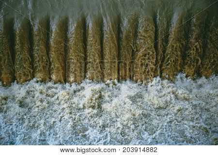 Powerful water flow on the man-made dam near the hydroelectric plant, water is boiling