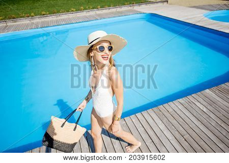 Lifestyle portrait of a woman in swimsuit with sunhat and bag walking outdoors near the swimming pool