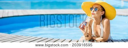 Young woman in swimsuit with big yellow sunhat relaxing with a bottle of fresh drink sitting on the poolside outdoors. Panoramic cropped image