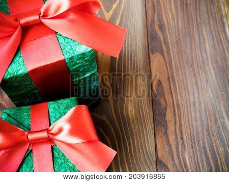 Gift boxes with red ribbons on wooden board. Holidays concept