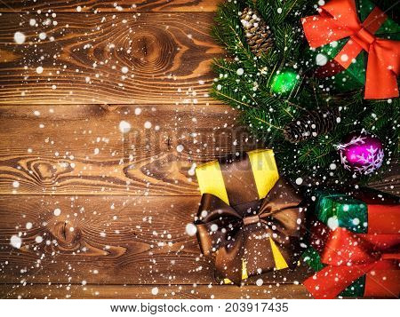 Christmas wreath of fir branches with cones and fir tree balls along with gift boxes on the wooden background. Drawn snow. Top view. Holiday concept