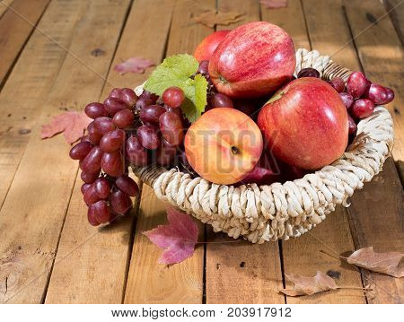 Basket of grapes apples and peach on a wooden surface