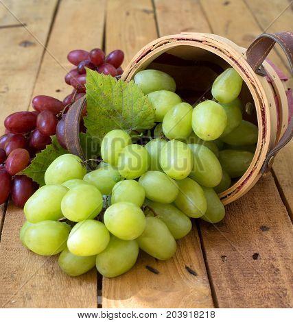 Spilled basket og white grapes on a wood surface